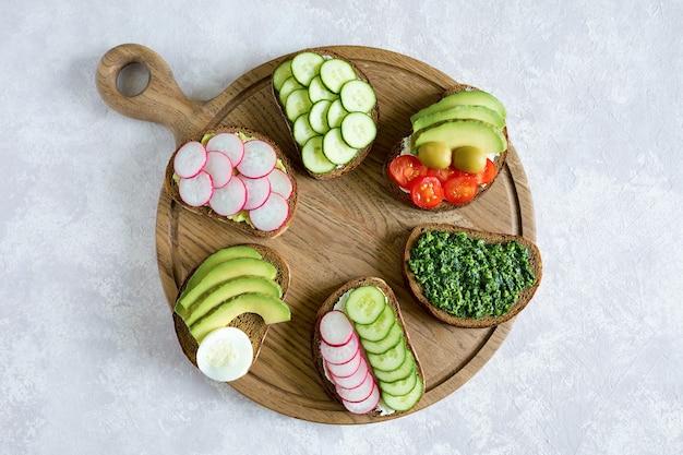 Vegetarische sandwiches auf dem holzbrett auf dem grauen hintergrund. leckeres frühstück. flache lage, draufsicht.