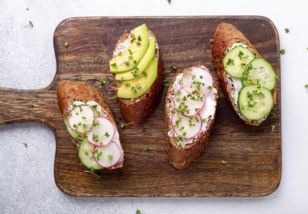 Vegetarische sandwiches auf einem holzbrett. frischkäse-, avocado-, gurken-, radieschen- und senf-mikrogrün. draufsicht. gesunder snack