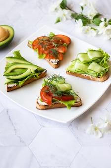 Vegetarische sandwiches mit avocado, tomaten und gurken auf hellem hintergrund