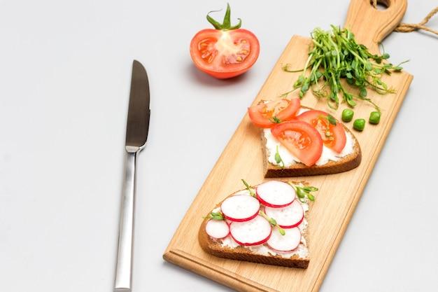 Vegetarische sandwiches mit tomaten und radieschen auf schneidebrett