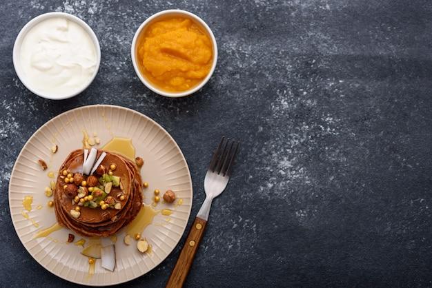 Vegetarische schokoladenpfannkuchen mit nüssen, ahornsirup, obst, mangomarmelade, sauerrahm auf grau