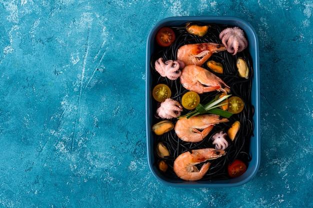 Vegetarische schwarze spaghetti der draufsicht mit riesengarnelen, muscheln, tintenfisch und gemüse in der blauen platte auf blauem hintergrund mit kopienraum