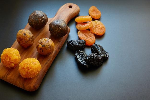 Vegetarische süße energiekugeln. getrocknete aprikosen, pflaumen, datteln, nüsse und rohe samen