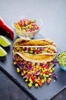 Vegetarische tacos mit verschiedenem gemüse, guacamole und geschnittenem kalk auf dunklem hintergrund. tacos mit zuckermais, purpurkohl und pfeffer auf einem schieferbrett. platz kopieren