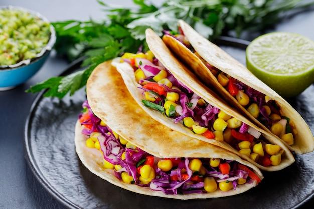 Vegetarische tacos mit verschiedenem gemüse, guacamole und limette auf dunklem hintergrund. tacos mit zuckermais, purpurkohl und tomaten auf einem schwarzen teller. nahaufnahme