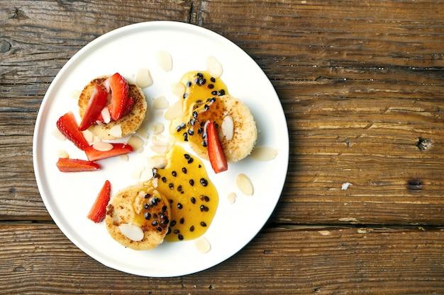Vegetarische tofu-käsekuchen mit mandeln, erdbeeren und passionsfruchtmarmelade auf holz