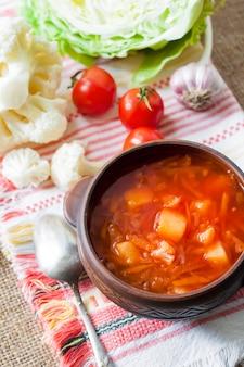 Vegetarische tomatensuppe mit kohl und blumenkohl in einer rustikalen keramikschale