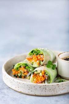 Vegetarische vietnamesische frühlingsrollen mit karotten, gurken, frühlingszwiebeln und reisnudeln selektiver fokus