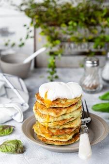 Vegetarische zucchini-krapfen oder pfannkuchen mit dill und pochiertem ei