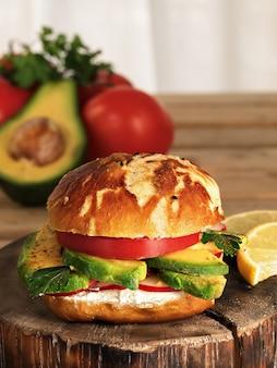 Vegetarischer burger mit avacado, radieschen, weichkäse und tomate auf einem teller. hausgemachtes brötchen mit samen. zutaten für einen burger. nahansicht.