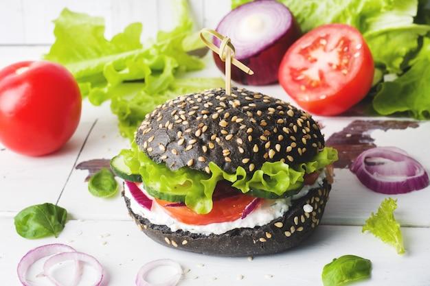 Vegetarischer burger mit hüttenkäsecreme und -gemüse.
