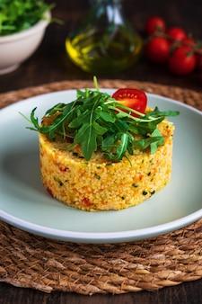 Vegetarischer couscous-salat mit gemüse, zucchini, karotten, gemüsepaprika, gewürzen. fitne
