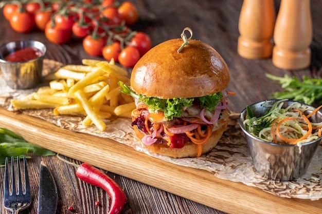 Vegetarischer frischer burger mit pilzen und gemüse, serviert mit pommes frites auf einem holzbrett, gesundes fast food