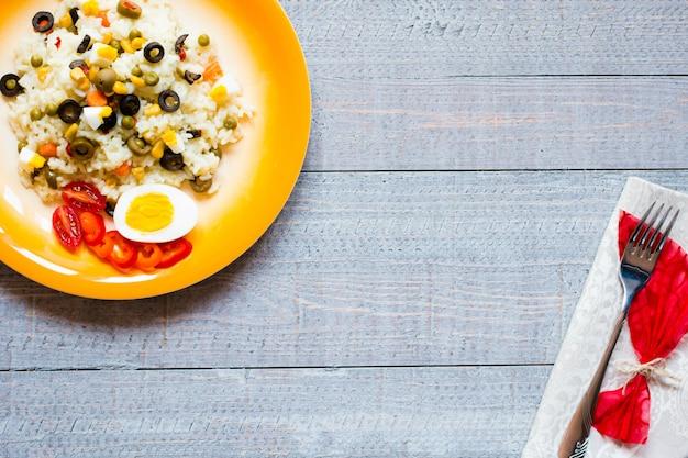 Vegetarischer frischer salat mit weißem reis auf hölzernem hintergrund