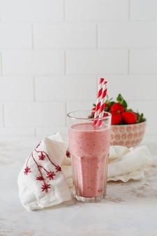 Vegetarischer gesunder smoothie von erdbeere mit beeren auf grauem oder weißem betonhintergrund. selektiver fokus. platz für text.