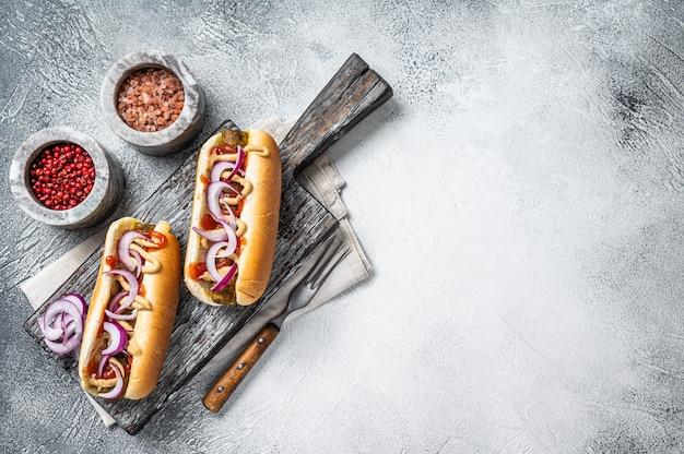 Vegetarischer hot dog mit toppings und fleischloser wurst. weißer hintergrund. ansicht von oben. platz kopieren.
