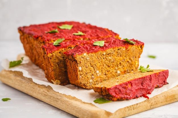 Vegetarischer linsenauflauf (in scheiben geschnitten) mit gemüse und tomatensauce auf einem holzbrett. gesundes veganes lebensmittelkonzept.