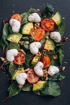 Vegetarischer mozzarellasalat in herzform mit avocado-, tomaten- und nusssauce