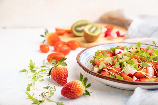 Vegetarischer obst- und gemüsesalat aus erdbeeren, kiwi, tomaten, mikrogrünen sprossen