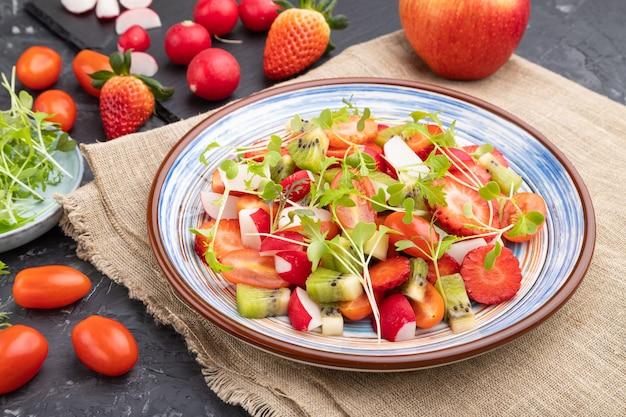 Vegetarischer obst- und gemüsesalat von erdbeere, kiwi, tomaten, mikrogrünen sprossen auf schwarzem betonhintergrund und leinentextil.