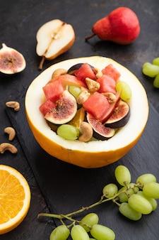 Vegetarischer obstsalat von wassermelone, trauben, feigen, birne, orange, cashew auf schieferbrett auf einem schwarzen betonhintergrund. seitenansicht, nahaufnahme.