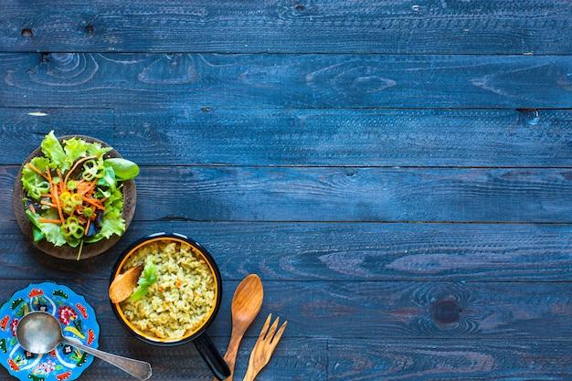 Vegetarischer risotto mit verschiedenem gemüse auf hölzerner rustikaler tabelle.