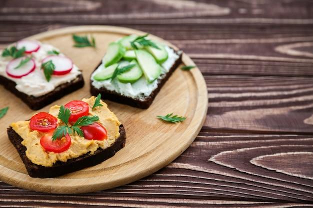 Vegetarischer roggenbrot-toast aus der nähe mit hüttenkäse, hummus, avocado, radieschen und tomate.