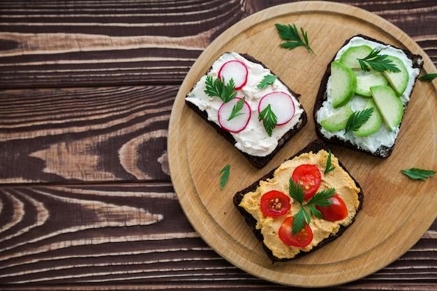 Vegetarischer roggenbrot-toast mit hüttenkäse, hummus, avocado, radieschen und tomate.