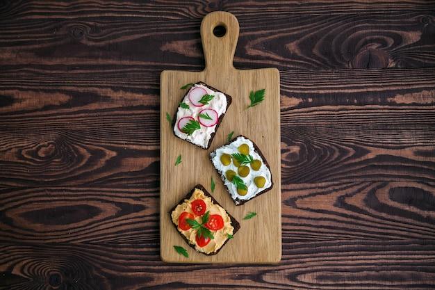 Vegetarischer roggenbrot-toast mit hüttenkäse, hummus, gurke, radieschen und tomate.