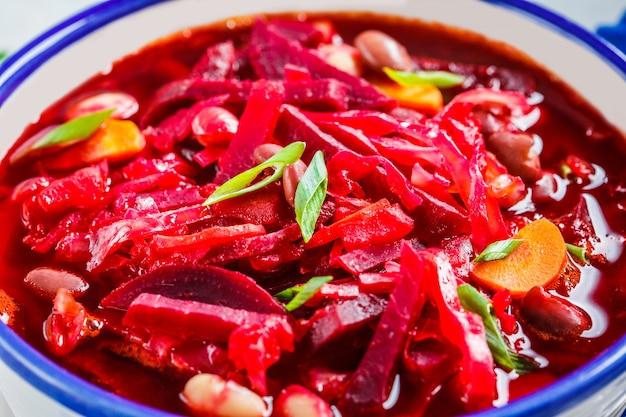 Vegetarischer rote-bete-suppen-borschtsch mit bohnen in der weißen schüssel auf weißer oberfläche, gesundes vegetarisches lebensmittelkonzept,