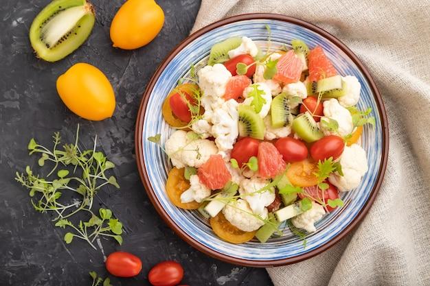 Vegetarischer salat aus blumenkohlkohl, kiwi, tomaten, mikrogrünen sprossen