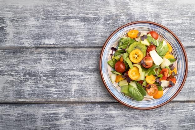 Vegetarischer salat aus pac choi kohl, kiwi, tomaten, kumquat, mikrogrünen sprossen
