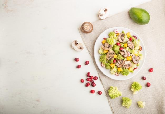 Vegetarischer salat aus romanesco kohl, champignons, cranberry, avocado und kürbis. draufsicht, copyspace.