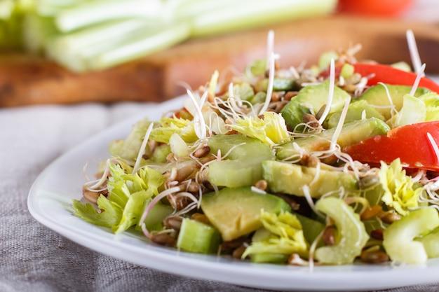 Vegetarischer salat aus sellerie, gekeimtem roggen, tomaten und avocado auf leinentischdecke.