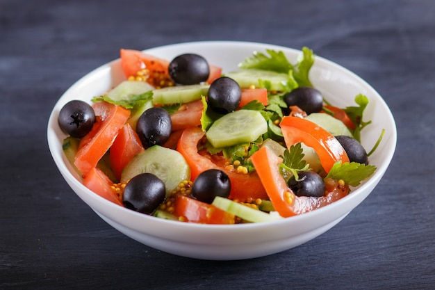 Vegetarischer salat aus tomaten, gurken, petersilie, oliven und senf auf schwarzem holz