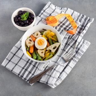Vegetarischer salat mit beeren und messendem band