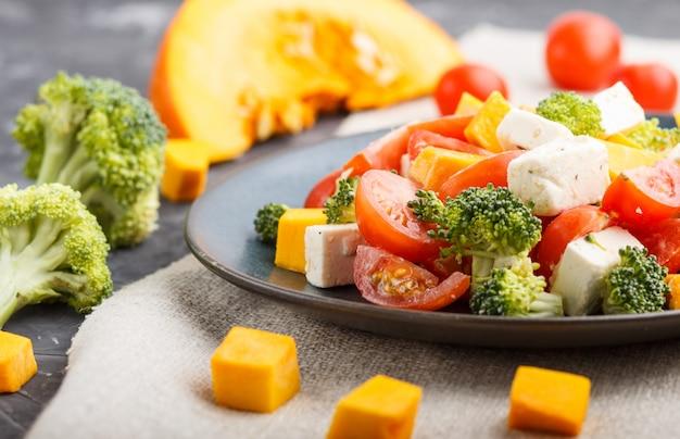 Vegetarischer salat mit brokkoli, tomaten, feta und kürbis auf einer blauen keramikplatte