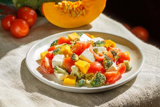 Vegetarischer salat mit brokkoli, tomaten, feta und kürbis auf weisser keramikplatte auf leinentextil,