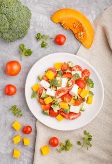 Vegetarischer salat mit brokkoli, tomaten, feta und kürbis auf weißer keramischer platte