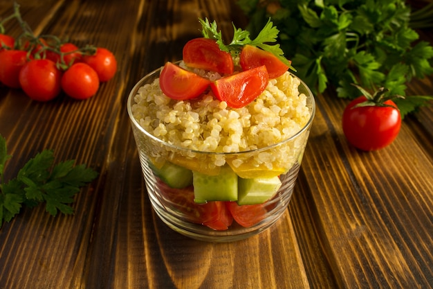 Vegetarischer salat mit gemüse und quinoa auf dem braunen holztisch