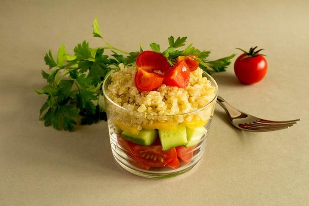 Vegetarischer salat mit gemüse und quinoa auf dem grauen hintergrund