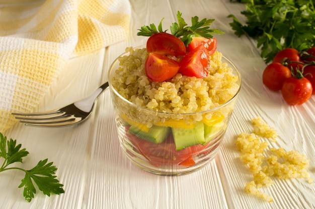 Vegetarischer salat mit gemüse und quinoa auf dem weißen hölzernen hintergrund