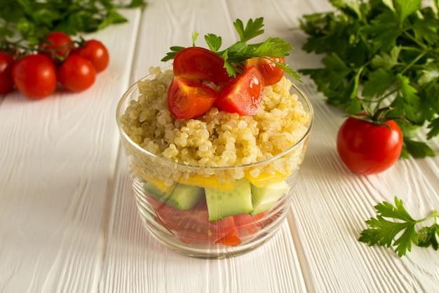 Vegetarischer salat mit gemüse und quinoa auf dem weißen holz