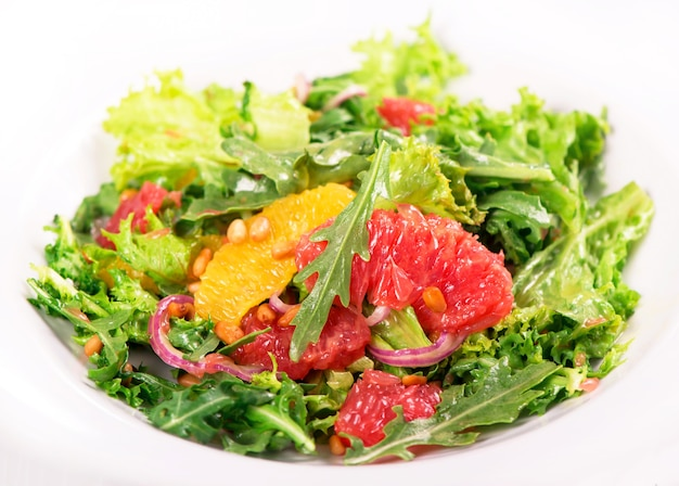 Vegetarischer salat mit grapefruit, orange, pinienkernen und einer mischung aus salatblättern