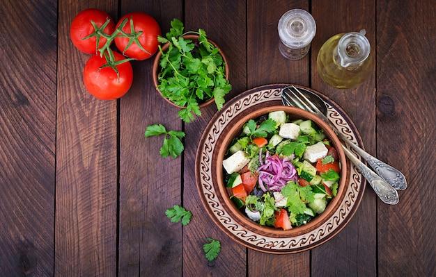 Vegetarischer salat mit kirschtomate, briekäse, gurke, koriander und roten zwiebeln
