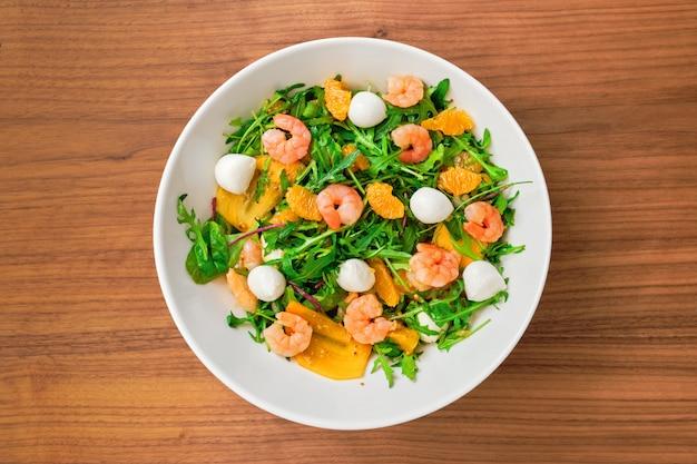 Vegetarischer salat mit rucola, persimone, mandarine, garnelen und mozzarella