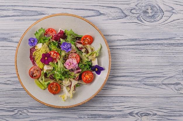 Vegetarischer salat mit tomaten, salat und käse, garniert mit essbaren blumen. frühlings-food-konzept. hintergrund mit kopierraum