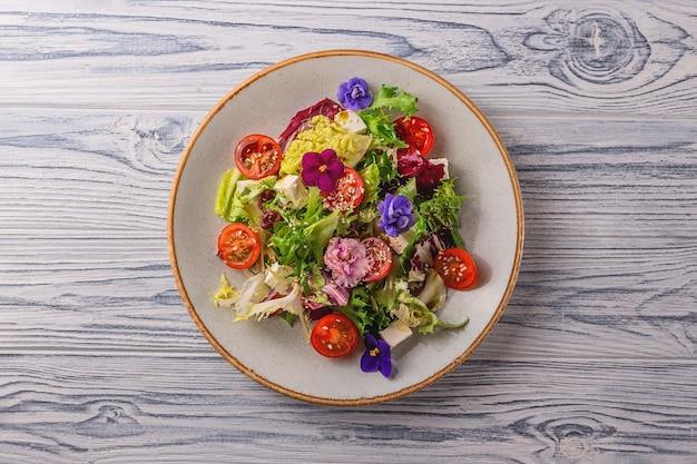 Vegetarischer salat mit tomaten, salat und käse, garniert mit essbaren blumen. frühlings-food-konzept.