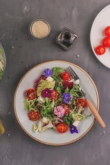 Vegetarischer salat mit tomaten, salat und käse, garniert mit essbaren blumen und zutaten auf einem grauen tisch. frühlings-food-konzept.