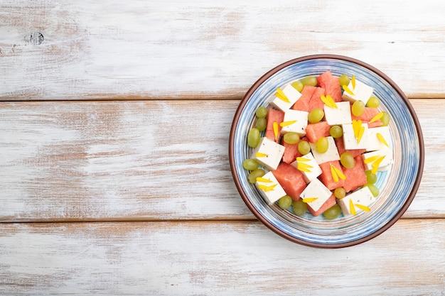 Vegetarischer salat mit wassermelone, feta-käse und trauben auf blauem keramikteller auf weißem holzhintergrund. draufsicht, kopierraum, flache lage.